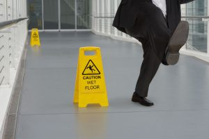34520627 - man in suit slipping on wet floor with several warning signs